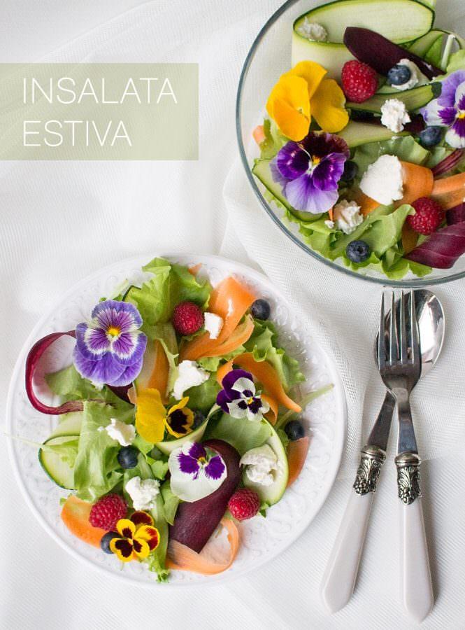 Insalata estiva con fiori, carote arancioni e viola, zucchine, frutta e caprino